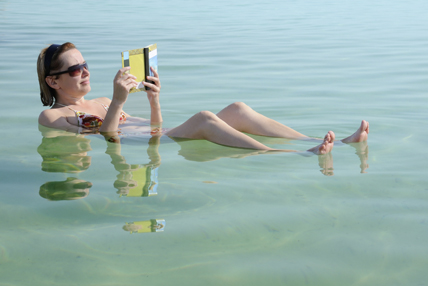 Caucasian woman reads a book floating in the waters of the Dead Sea in Israel