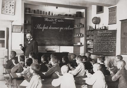 Une classe de garçons en 1900. Chaque élève apprend à tenir son porte-plume avec 3 doigts. (© Musée national de l'éducation - CNDP)