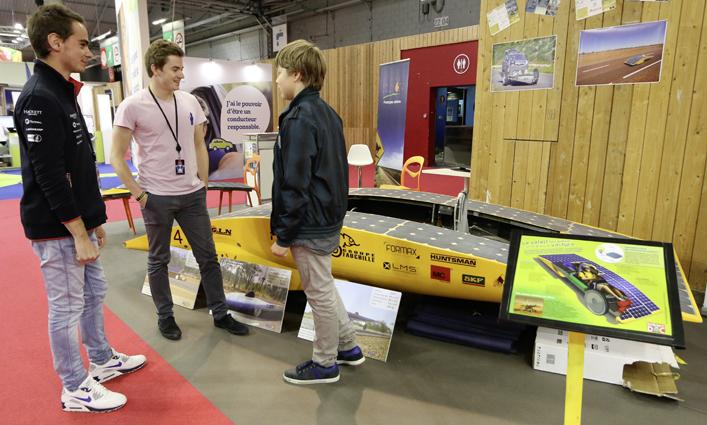 Michaël (13 ans) se renseigne sur la voiture solaire Hélios IV, auprès d'Antoine et Mathieu, élèves ingénieurs à l'HEI de Lille. Photo Marc Beynié. Illustration Pierre-Marie Valat