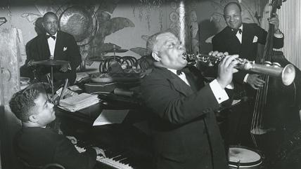 Dans les années 1940, Sidney Bechet joue de la clarinette avec 3 amis, pianiste, batteur et contrebassiste. © S. Bechet Productions / Jazzitude